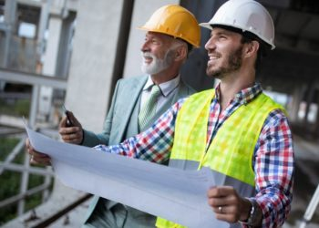 Construction engineer architect with foreman worker checking construction site